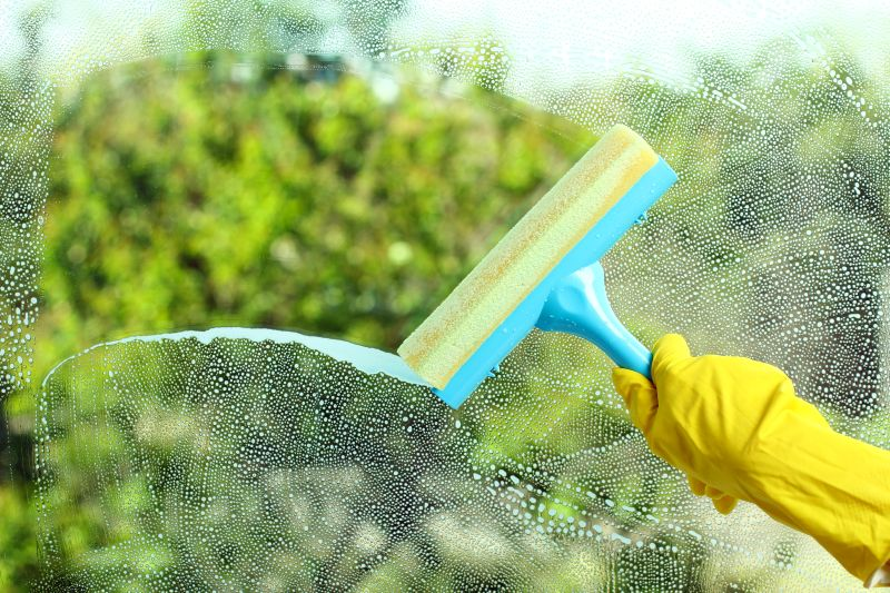 Hand in a yellow glove with special tool washes the soap window on the background of trees