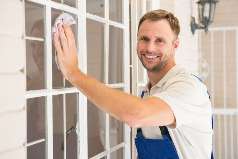 33949766 - handyman cleaning the window and smiling in a new house