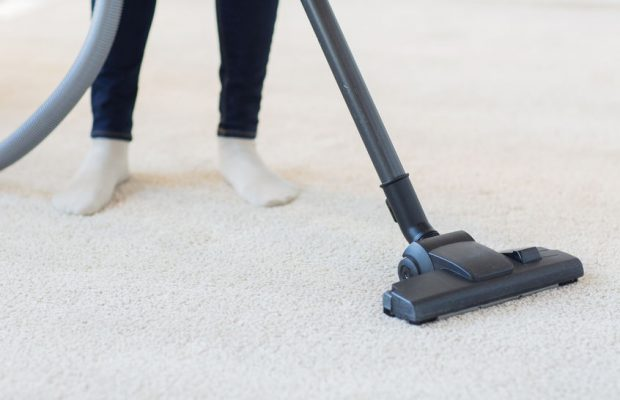 38676105 - people, housework and housekeeping concept - close up of woman with legs vacuum cleaner cleaning carpet at home