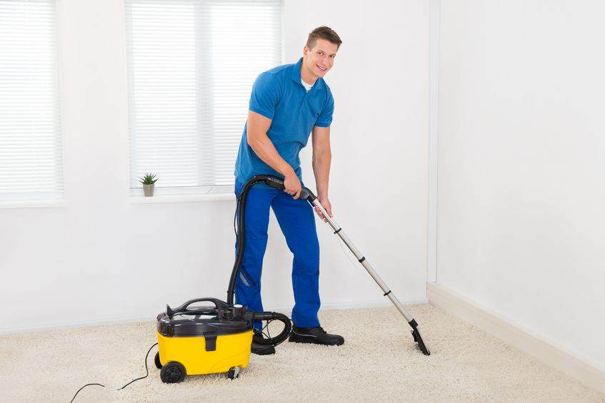 44713298 - happy male janitor cleaning carpet with vacuum cleaner
