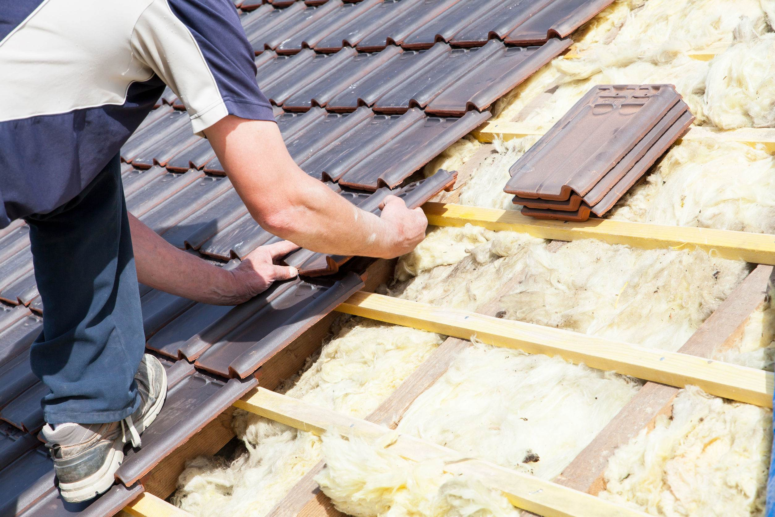 40105407 - a roofer laying tile on the roof